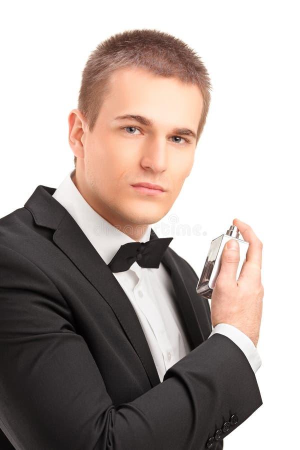 En stående av en stilig manlig i svart passar genom att använda parfume royaltyfria foton