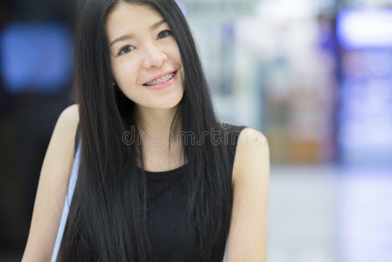 En stående av en ung asiatisk kvinna som ler till kameran arkivbild