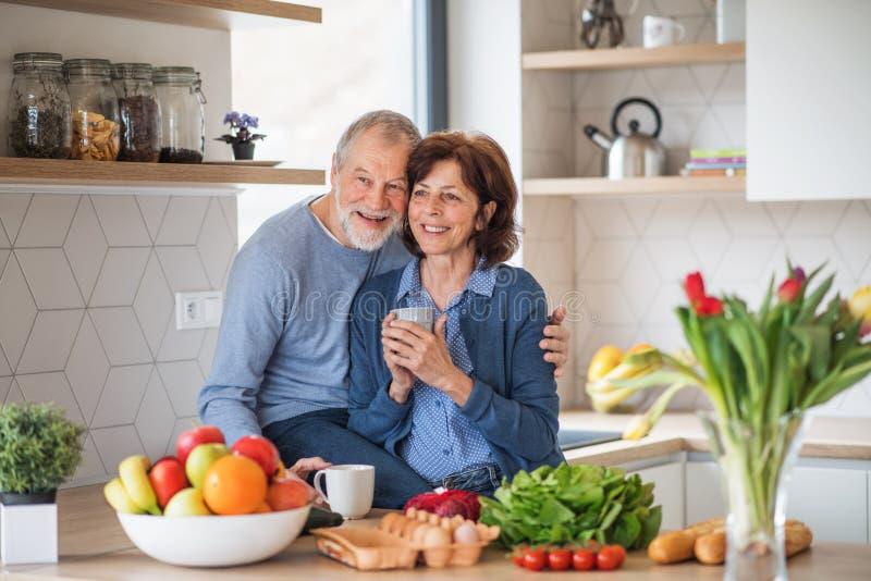 En stående av förälskade höga par inomhus hemma som rymmer kaffe royaltyfria foton