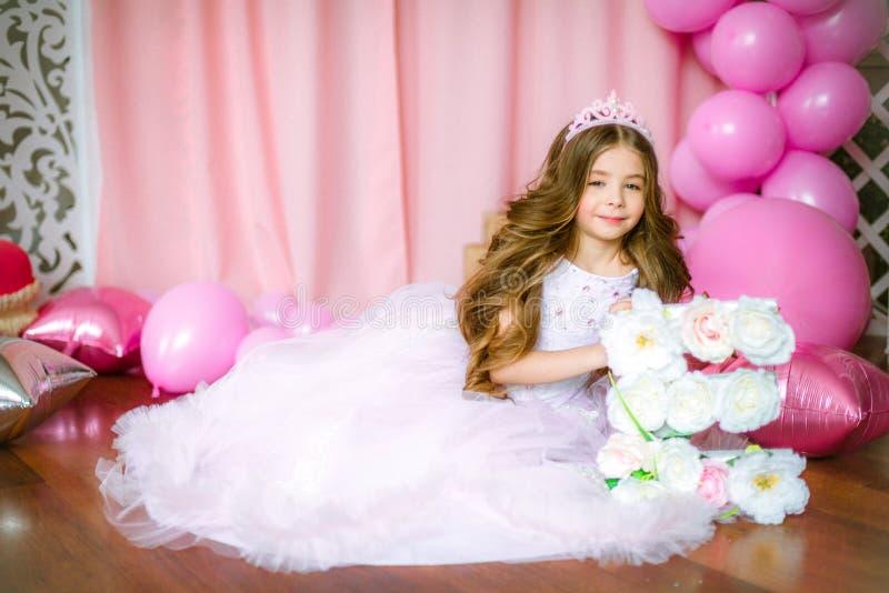 En stående av en härlig liten flicka i en studio dekorerade många färgballonger royaltyfri foto