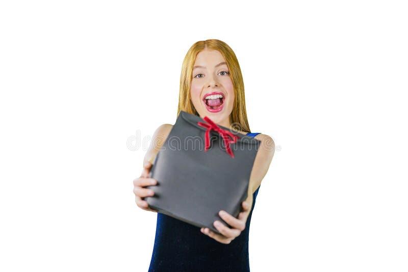 En stående av en härlig ung rödhårig flicka i en aftonklänning, som rymmer en gåva i hans armar, ler arkivbild