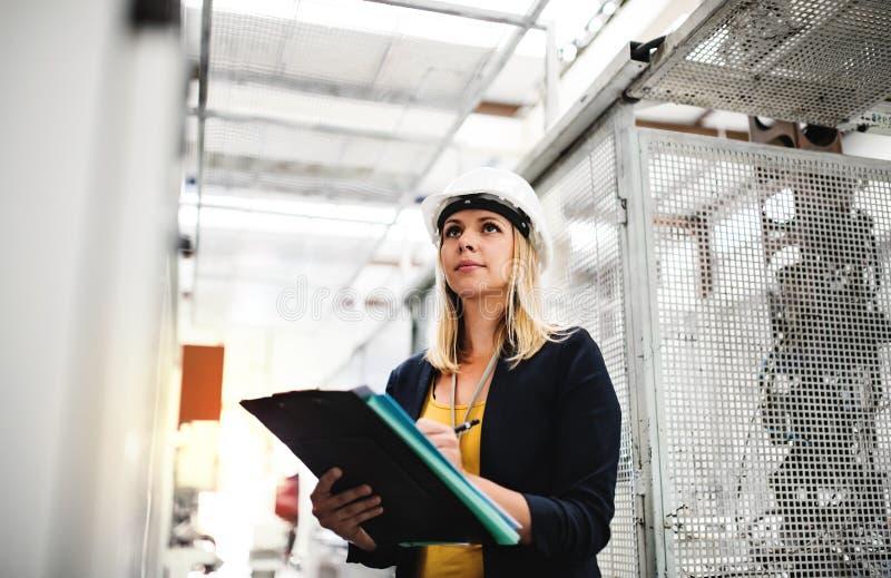 En stående av en industriell kvinnatekniker i en fabrik som kontrollerar något fotografering för bildbyråer