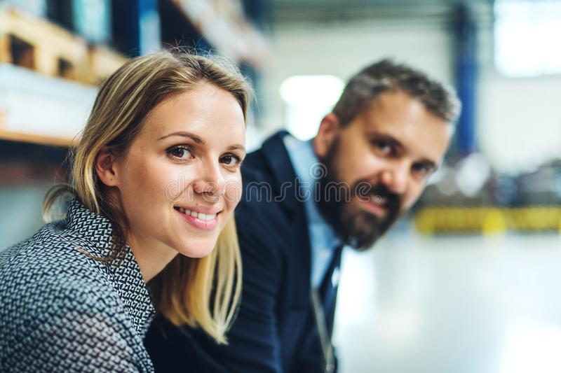 En stående av en industriell man- och kvinnatekniker i en fabrik som ser kameran arkivbild