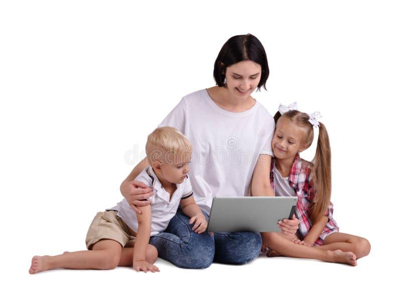 En stående av en lycklig familj som isoleras på en vit bakgrund En le moder med hennes lilla ungar som rymmer en bärbar dator royaltyfria foton