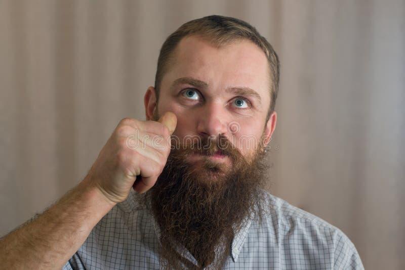 En stående av en man med ett långt skägg som vrider hans mustasch fotografering för bildbyråer