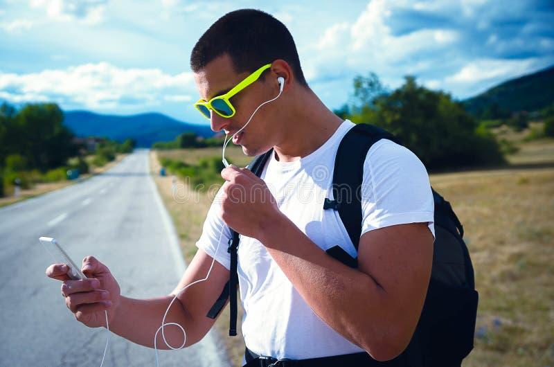 En stående av en man som rymmer en telefon och talar över hörlurar arkivbild