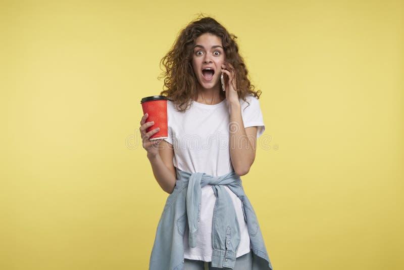 En stående av smartphonen och innehavet för upphetsad brunett den kvinnliga talande per koppen kaffe i handen arkivbild