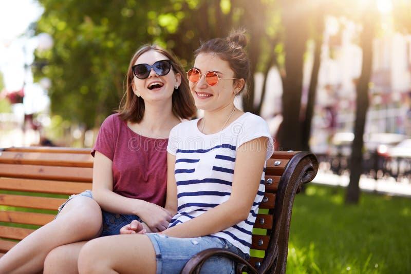 En stående av två attraktiva unga vänner, som har att vila på träbänk i lokal, parkerar efter långt går Skratta har flickor lotte royaltyfri fotografi