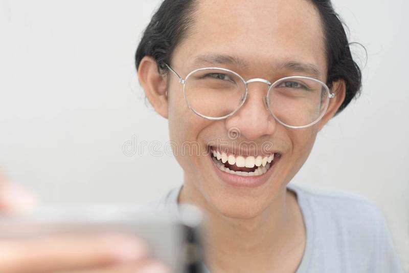 En stående av en ung attraktiv man som tar bilder av honom själv- eller selfiestund, ger upp tummen arkivbilder
