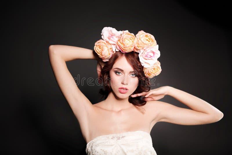 En stående av en ung härlig kvinna med blommor på huvudet arkivfoton