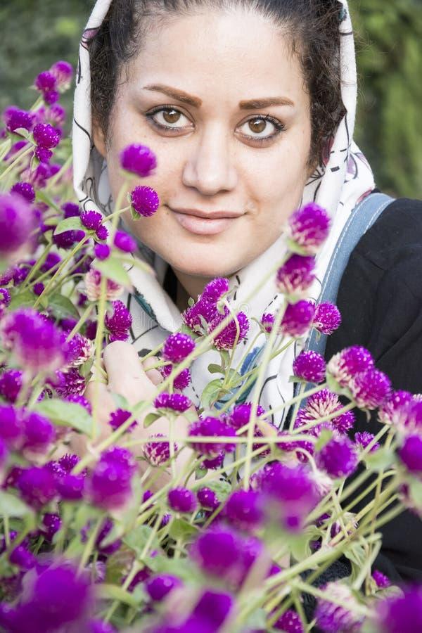En stående av en ung härlig muslim kvinna i en vit sjal framme av det vertikala skottet för purpurfärgade blommor royaltyfri bild