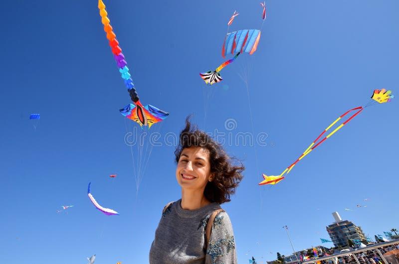 En stående av en ung kvinna med drakarna Festival av vindarna, Bondi strand, Sydney, Australien arkivfoto