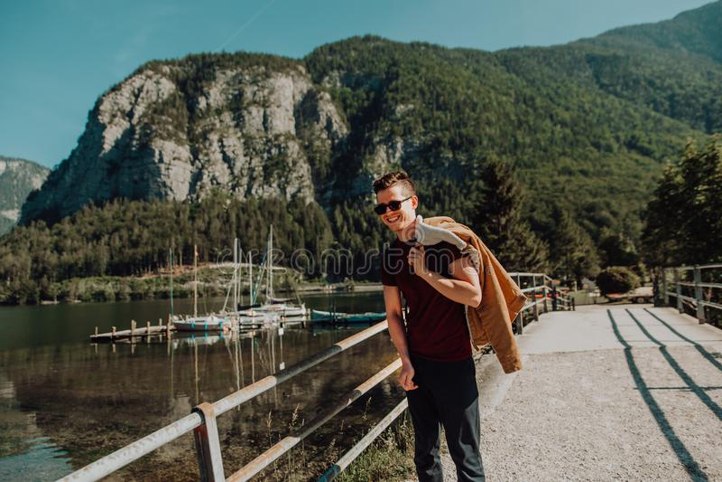 En stående av en ung lycklig man framme av en bergsjö royaltyfri bild