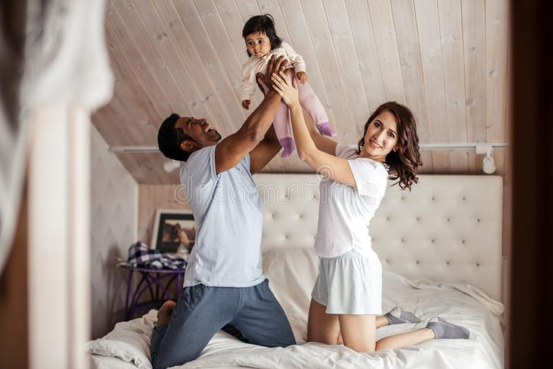 En stående av unga par som tillsammans lyfter deras lilla barn royaltyfri bild