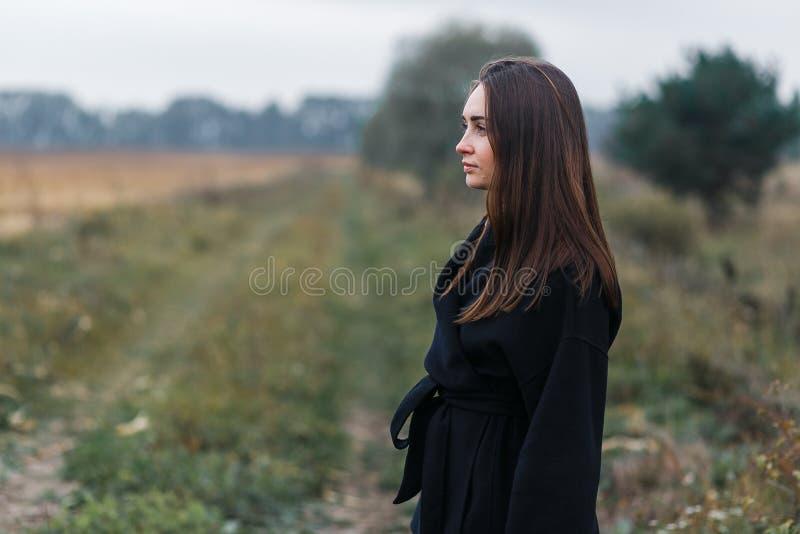 En stående för ung kvinna med bygräsvägen på bakgrund Molnigt höstväder arkivbilder