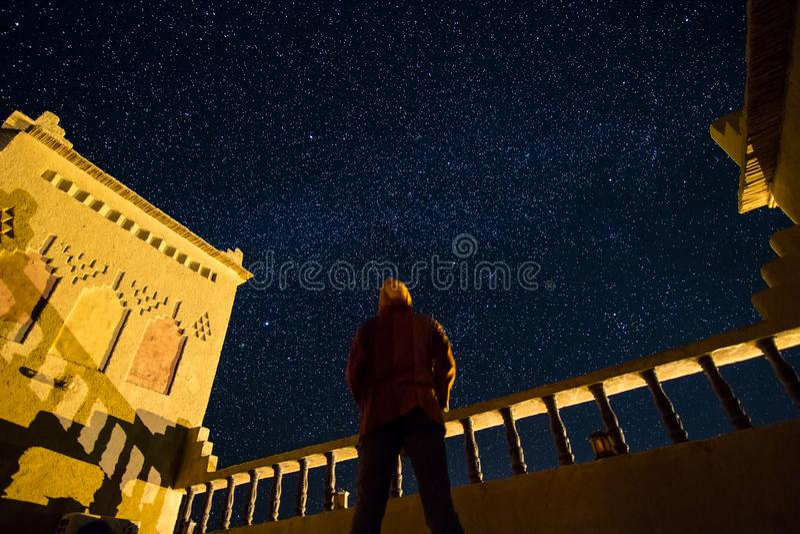 En stående man som ser den stjärnklara himlen på taket av en kasbah i sydliga Marocko royaltyfri foto