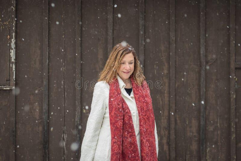 En stående yttersida för kvinna vid den wood sidingen för brun ladugård som ljus fl arkivfoton