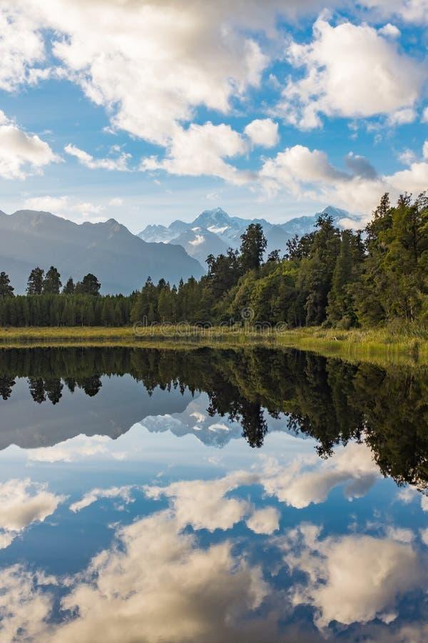 En ståendesikt av den incredibly härliga sjön Matheson som är nyazeeländsk med reflexionen av de bedöva sydliga fjällängarna arkivfoto
