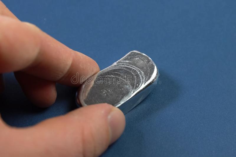 En stång av aluminium i hans hand Spilld aluminum tacka royaltyfria foton