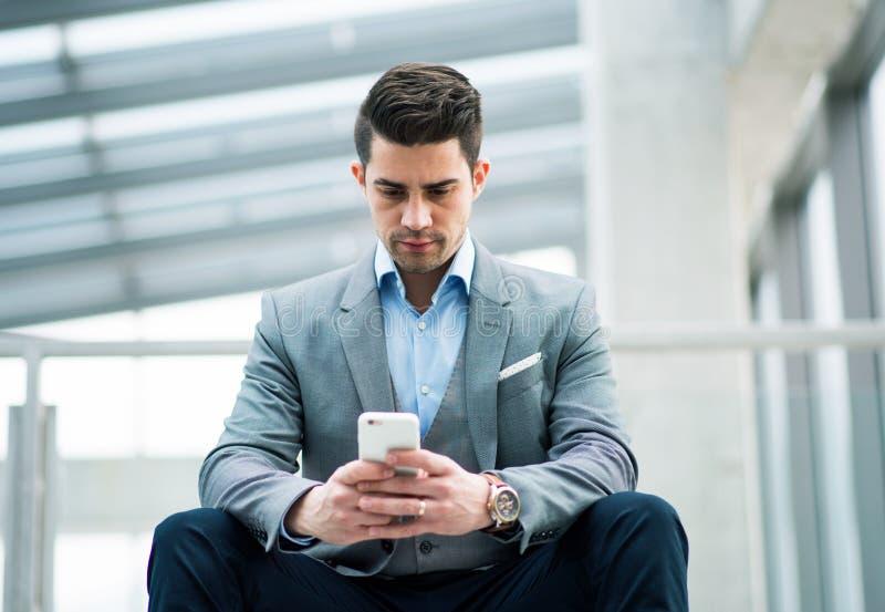 En st?ende av den unga aff?rsmannen med smartphonen som sitter i korridor utanf?r kontor arkivbilder