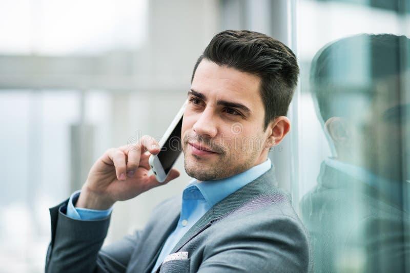 En st?ende av den unga aff?rsmannen med smartphonen som sitter i korridor utanf?r kontor royaltyfri foto