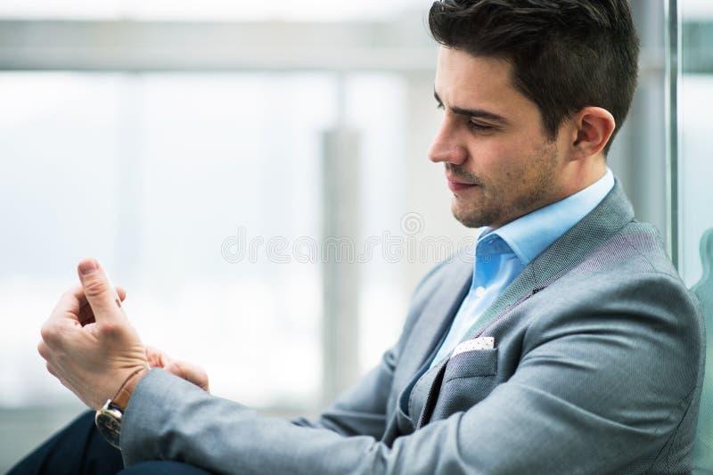 En st?ende av den unga aff?rsmannen med smartphonen som sitter i korridor utanf?r kontor arkivbild
