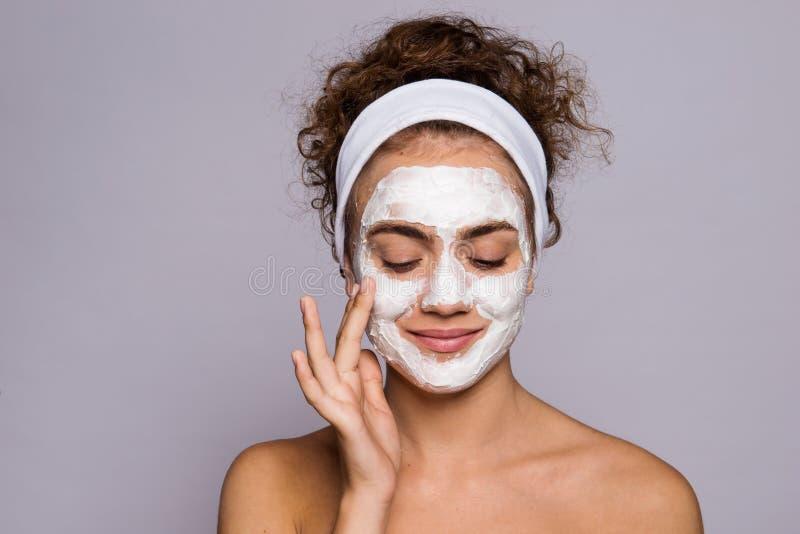 En st?ende av en ung kvinna med maskeringen i en studio, en sk?nhet och en hudomsorg royaltyfri bild