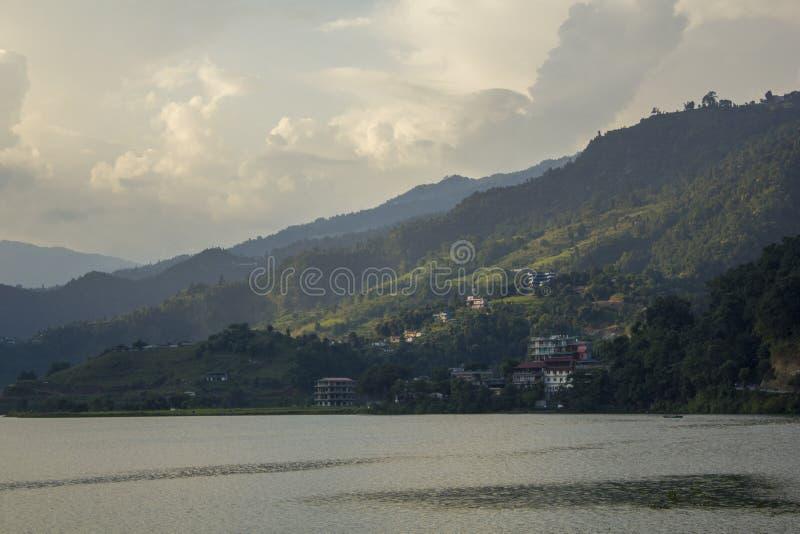 En stad inhyser på en grön berglutning under en molnig himmel i aftonen mot en sjö arkivbilder