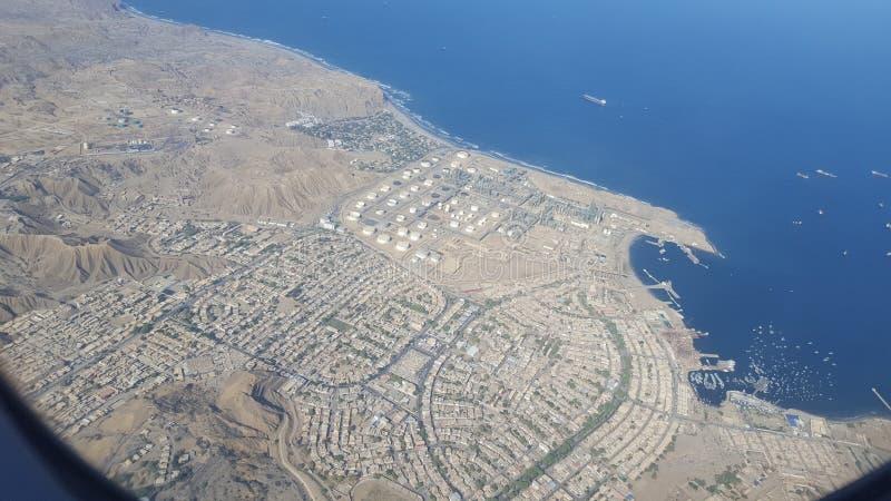 En stad och en raffinaderi vid havet med en str?lpunkt arkivbilder
