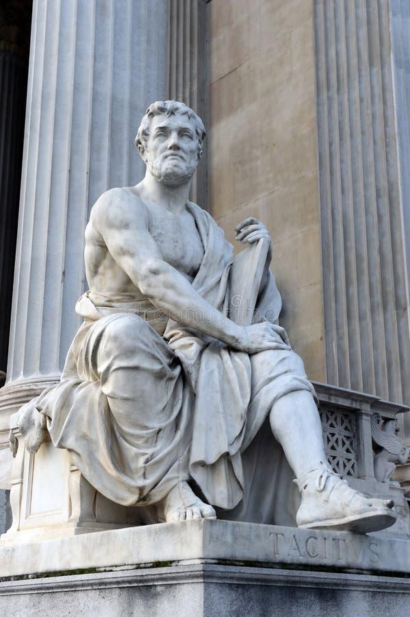 En staty av den romerska historiker Tacitus mot byggnaden av den österrikiska parlamentet arkivfoto