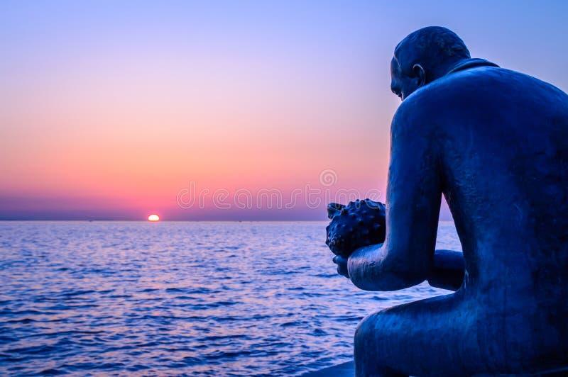 En staty av en man som rymmer ett havsskal vid havet på solnedgången royaltyfri fotografi