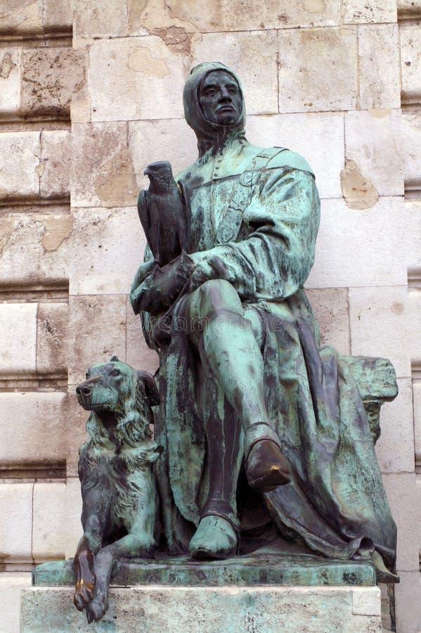 En staty av en placerad man med en falk på hans hand och en hund på hans fot arkivbild