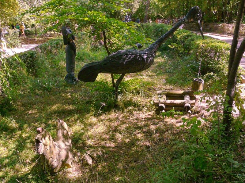 En staty av en träkran som tar en hink av vatten från brunnen Utställning i parkera royaltyfri bild