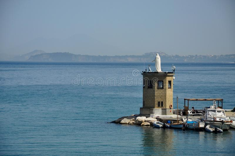 En staty i havet och fiskebåtar på ön av Procida, Naples/Italien arkivbild