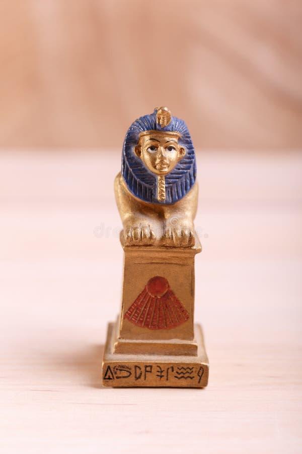 En statyett av en sfinx med blå man royaltyfria bilder