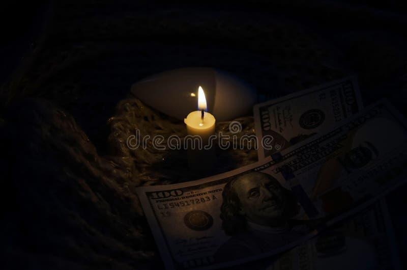 En stearinljus, en ljus kula, dollar på en varm halsduk royaltyfria bilder