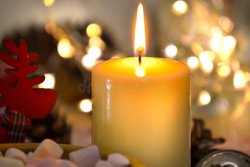 En stearinljus som ljust bränner i mörkret mot en bakgrund av oskarpa ljus Romansk festlig afton royaltyfri bild