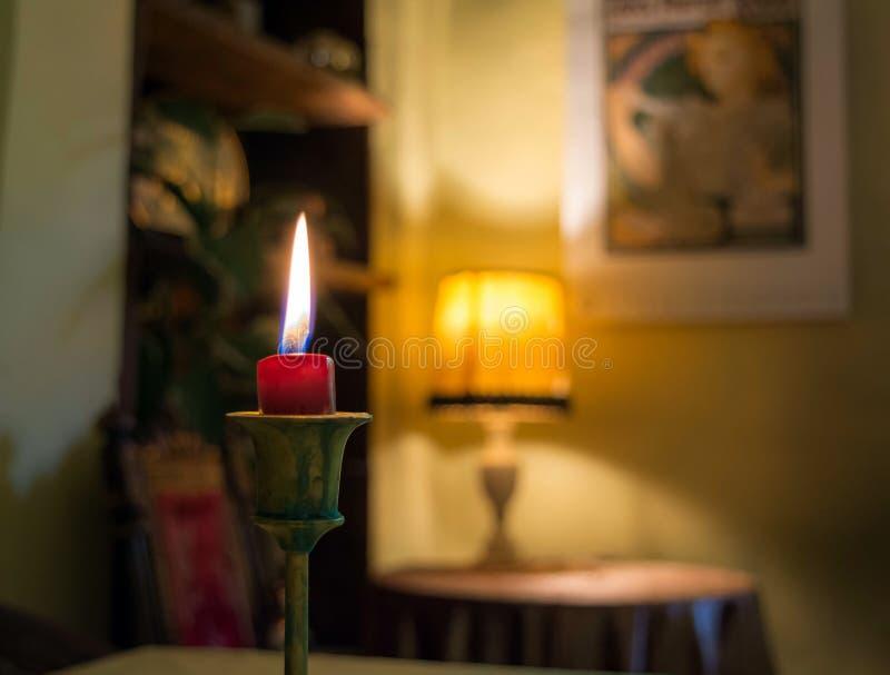 En stearinljus som ljust inomhus bränner med bokehbakgrund royaltyfri foto