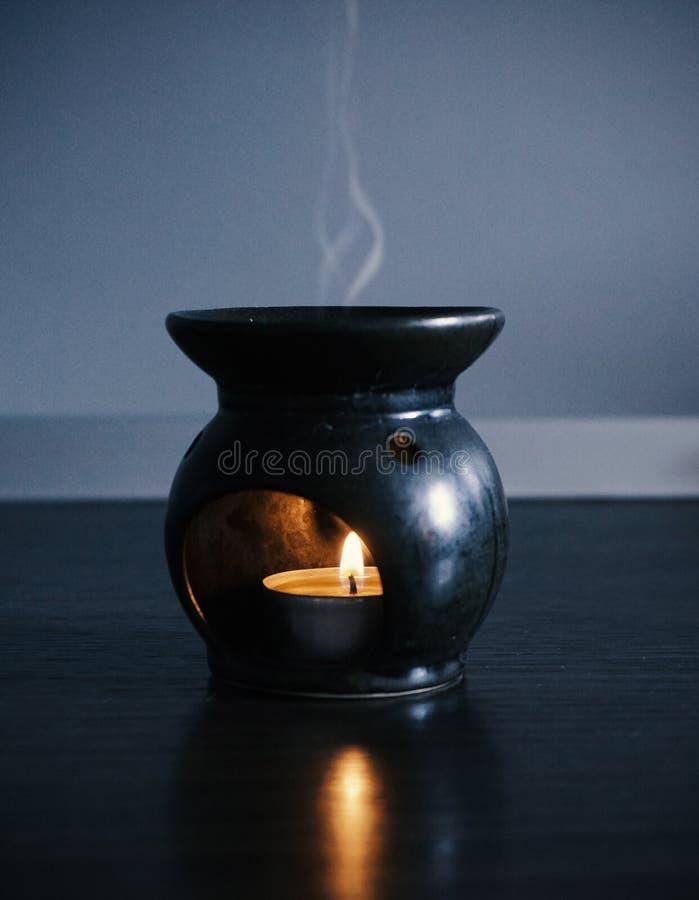 En stearinljus, som värmer en doftande olja, med ånga arkivfoto