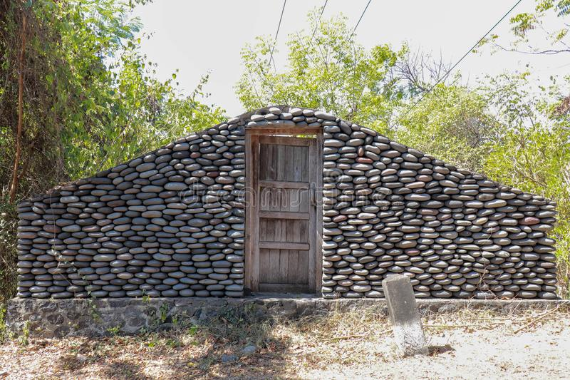 En stenblockvägg med stängda trädörrar Stenvägg vid vägen i den Bali ön, Indonesien Skriv in djungeln Mystiskt ställe med M arkivfoto