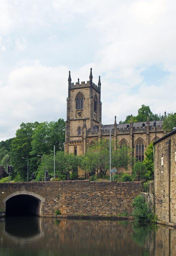 En stenbro som korsar kanalen i den västra sowerby bron - yorkshire med den historiska christ kyrkliga byggnaden som omges av trä royaltyfria foton