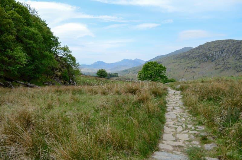 En stenig bana på assistentsidan av bildblytak över grässlätt till berg i Snowdonia royaltyfria bilder