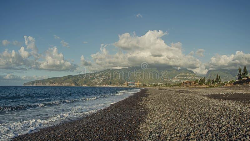 En stenig strand och stora gröna kullar under molnen, Le Port royaltyfri foto