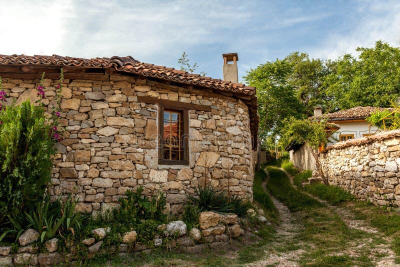 En stenvägg och ett gammalt hus från Arbanasi, Bulgarien. arkivfoton