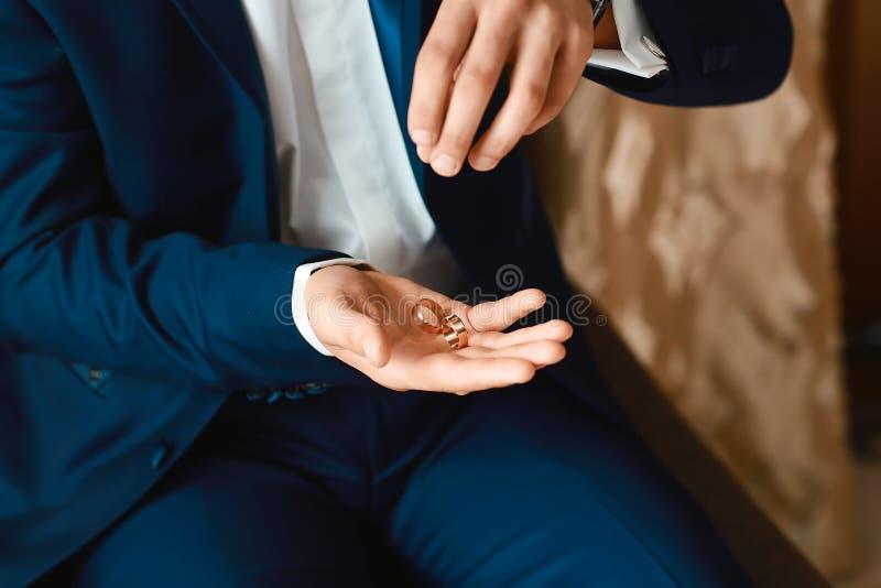 En stilfull brudgum i ett mörkt - den blåa dräktdräkten kastar att gifta sig guld- cirklar från hennes händer arkivfoton