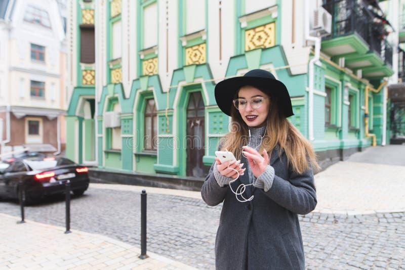 En stilfull kvinna använder telefonen på bakgrunden av den härliga arkitekturen av den gamla staden royaltyfri fotografi