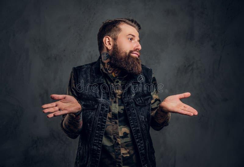 En stilfull skäggig grabb med tatuerade händer i den militära skjorta- och grov bomullstvillvästen som poserar med en förbryllad  royaltyfria foton