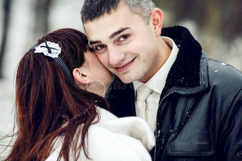 En stilig brudgum ler, medan en brud döljer hennes framsida under hans c royaltyfria bilder