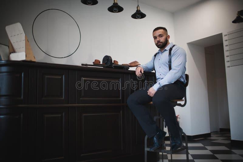 En stilig gangster i en blå skjorta En stående av ett säkert mördaresammanträde bredvid vapnet på en vit väggbakgrund arkivbilder