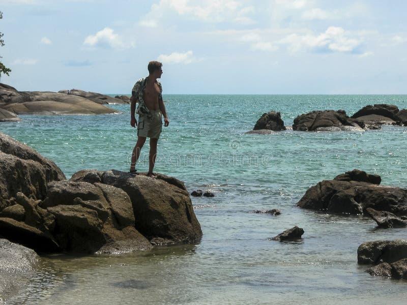 En stilig grabb i en skjorta str?cks p? vaggar och ser bort Exotisk havssikt L?s strand med stora stenar arkivfoto